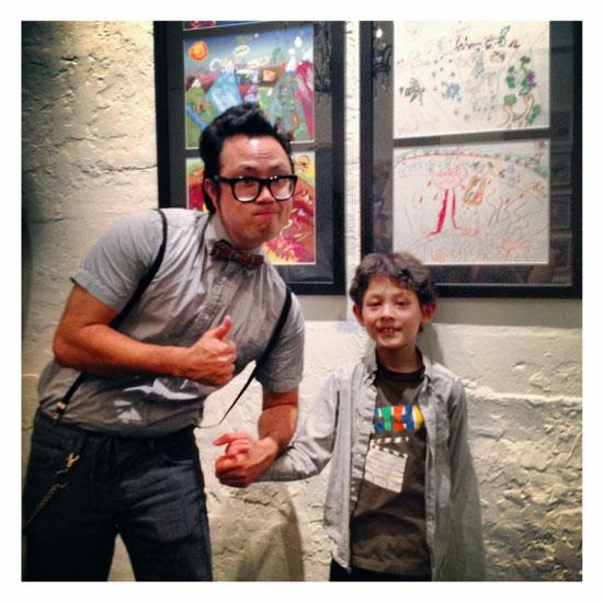 "Jerome Lu and Braden Cruz in front of their collaborative piece, ""The World and Its Many Wonders!"""