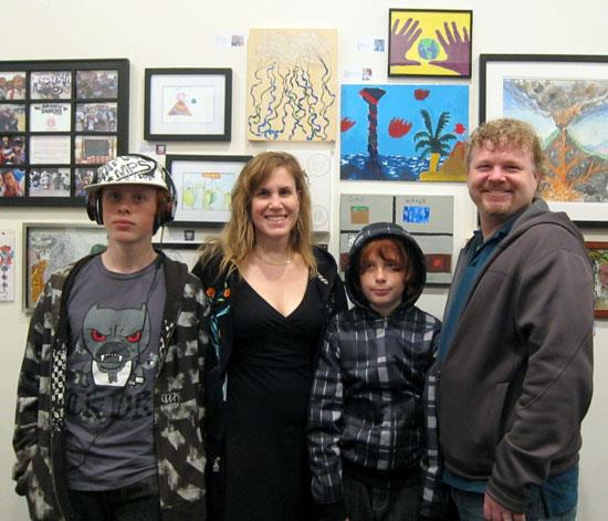 "Matthew Rhodes (and family) in front of his painting, ""Beautiful Disaster"""