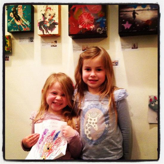 "Kids Art: Chloe and Isobel standing below their paintings ""Night Light"" and ""A Day at the Beach"". EARTH MOVEMENT trivia: Chloe is holding a coloring sheet by Sergey and iLusha Safonov!"
