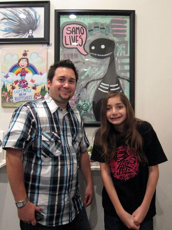 "Chris Avalos and Cooper in front of ""Samo Lives"" by Chris, Xander and Bella"