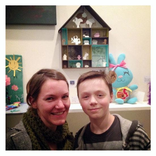 "Julie West and James in front of their mixed media piece, ""One World, One Home"""