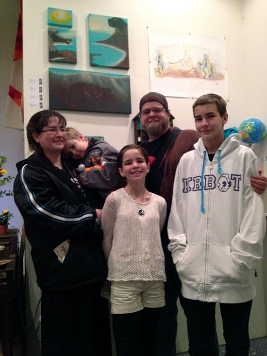 The Valleydweller clan with Timothy, Kathryn, Jeremy and Ethan in front of their paintings